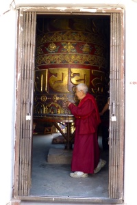 Monk spinning a massive prayer wheel in Boudha