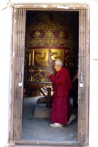 Monk spinning a massive prayer wheel in Boudha